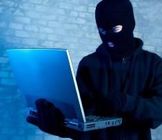 A Hacker looking at a laptop